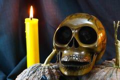 Menschliche Schädel und Kürbis auf schwarzem Hintergrund, Halloween-Tageshintergrund Lizenzfreie Stockfotos