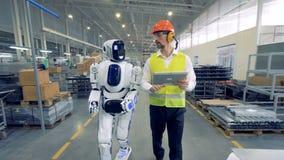 Menschlicher Arbeiter und ein Roboter gehen zusammen in Fabrikvoraussetzungen stock video footage