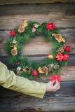 Menschlicher dekorativer roter Bogen der Armholding nahe Weihnachtskranz im Freien am Blockhauswandhintergrund Lizenzfreie Stockfotos