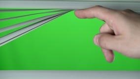 Menschlicher Finger hebt den Jalousie oben an Grüner Bildschirm stock footage