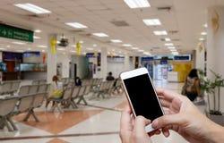 Menschlicher haltener leerer Bildschirm von Smartphone und von Warteankunftszeithintergrundunschärfe Lizenzfreies Stockfoto