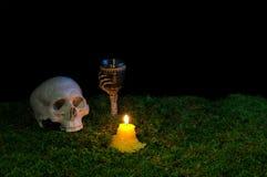 Menschlicher Schädel, Becher und Kerzen Halloweens, die an in die Dunkelheit glühen Stockfotografie