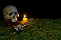 Menschlicher Schädel, Becher und Kerzen Halloweens, die an in die Dunkelheit glühen Lizenzfreie Stockfotografie