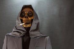 Menschlicher Schädel, der eine Zigarette auf einem schwarzen Hintergrund, Zigarette sehr gefährlich für Leute raucht Bitte rauche Stockfotos