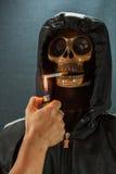 Menschlicher Schädel, der eine Zigarette auf einem schwarzen Hintergrund, Zigarette sehr gefährlich für Leute raucht Bitte rauche Stockbilder