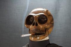 Menschlicher Schädel, der eine Zigarette auf einem schwarzen Hintergrund, Zigarette sehr gefährlich für Leute raucht Bitte rauche Lizenzfreie Stockfotos