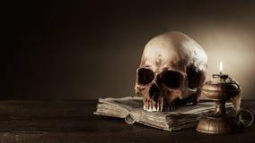Menschlicher Schädel und altes Buchstillleben Stockfotos