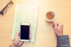 Menschlicher trinkender Kaffee He& x27; s unter Verwendung des Handys u. x28; Weinlese tone& x29; Lizenzfreies Stockbild