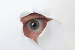 Menschliches Auge, das durch ein Loch im Papier schaut lizenzfreies stockbild
