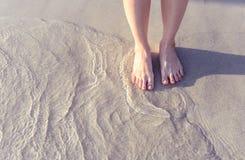 Menschliches Bein auf dem Strand mit Weinleseart Stockbilder