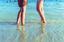 Menschliches Bein auf dem Strand mit Weinleseart Lizenzfreie Stockbilder