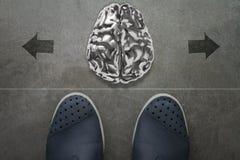menschliches Gehirn des Metall 3d auf Front von Geschäftsmannfüßen Lizenzfreies Stockfoto
