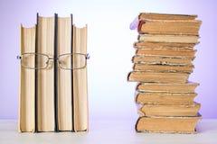 Menschliches Gesicht gemacht von einigen Büchern mit Gläsern, mit Stapel von alten schäbigen Büchern Das Konzept der Lesung lizenzfreie stockbilder
