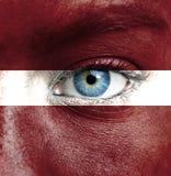 Menschliches Gesicht gemalt mit Flagge von Lettland lizenzfreies stockbild