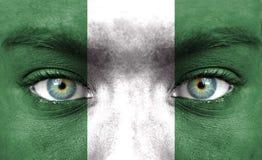Menschliches Gesicht gemalt mit Flagge von Nigeria lizenzfreies stockbild