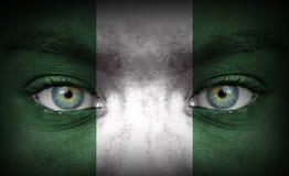 Menschliches Gesicht gemalt mit Flagge von Nigeria stockfotografie