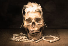 Menschliches Schädel- und Perlenhalskettenstillleben Lizenzfreie Stockfotos