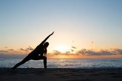 Menschliches Schattenbild, das Yoga auf dem Strand an der Dämmerung tut stockfotos