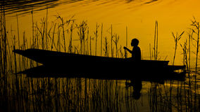 Menschliches Schattenbildrudersport auf dem Boot über dem drastischen Sonnenuntergang, menschlich Lizenzfreie Stockbilder