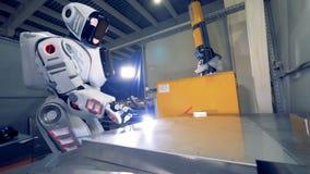 Menselijk-als robot last de lasser een metaalplaat bij een fabrieksvloer