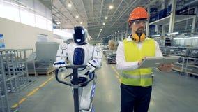 Menselijk-als robot trekt een fabrieksvervoerder terwijl het lopen samen met een fabrieksarbeider stock footage