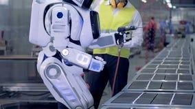 Menselijk-als robotbegin die met een boor na een overeenkomstig bevel van een fabrieksarbeider werken stock videobeelden