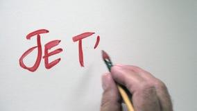 Menselijk hand het schrijven woord JE T'AIME in Frans, met rode gouache stock videobeelden