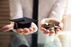 Menselijke de Graduatiehoed van de Handholding en Gouden Muntstukken royalty-vrije stock foto's