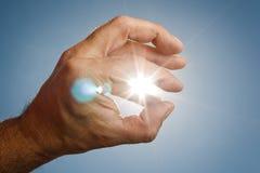 Menselijke hand die de zon probeert te grijpen Royalty-vrije Stock Afbeeldingen