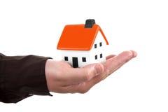 Menselijke hand die een huis houdt stock afbeelding