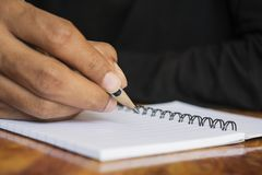 Menselijke hand die een nota schrijven stock afbeeldingen