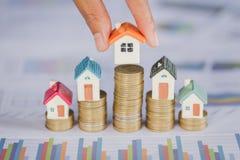 Menselijke hand die huismodel op muntstukkenstapel zetten Concept voor bezitsladder, hypotheek en onroerende goedereninvestering stock afbeelding