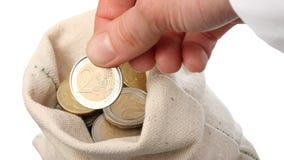 Menselijke hand die muntstuk zetten in een zak Royalty-vrije Stock Foto