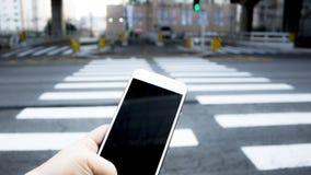 Menselijke hand die smartphone gebruiken bij zebrapad wanneer dwarsteken royalty-vrije stock afbeeldingen