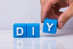 Menselijke Hand die Word Diy met Blauwe Kubieke Blokken maken royalty-vrije stock foto's