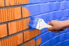 Menselijke hand het schilderen muur met blauwe kleur Royalty-vrije Stock Afbeelding