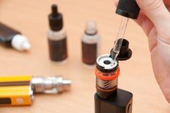 Menselijke hand het vullen e-vloeistof in het vaping van verstuiver Stock Afbeelding