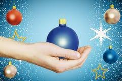 Menselijke hand met de blauwe bal van de Kerstmisboom met kleurrijke ballen bij Stock Fotografie