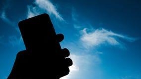 Menselijke hand met het silhouet van smartphoneschaduwen op heldere hemel, technologie-concept royalty-vrije stock afbeelding