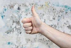 Menselijke hand op de achtergrond van een oude witte muur, duim omhoog stock foto's