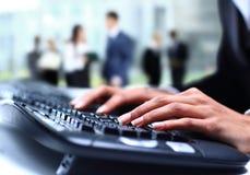 Menselijke handen die aan laptop op bureau werken Stock Foto's