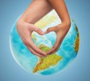 Menselijke handen die hartvorm over aardebol tonen Royalty-vrije Stock Foto's
