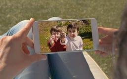 Menselijke handen die het mobiele bekijken een beeld van twee tweelingkinderen houden stock fotografie