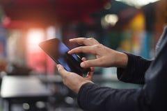 Menselijke handen die mobiele smartphone in koffiewinkel gebruiken stock afbeeldingen