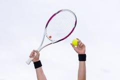 Menselijke handen die tennisbal en een racket op achtergrond van Th houden Royalty-vrije Stock Foto