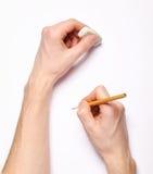 Menselijke handen met potlood en gom stock foto's