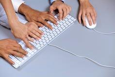Menselijke handen op computertoetsenbord met één hand die computermuis met behulp van Stock Foto