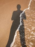 Menselijke schaduw op het zand stock afbeelding