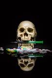Menselijke schedel in de stapel van drugs Stock Fotografie