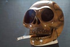 Menselijke schedel die een sigaret op een zwarte achtergrond, Sigaret roken zeer gevaarlijk voor mensen Gelieve te roken niet Hal Royalty-vrije Stock Afbeeldingen